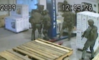 Partial warehouse video of raid; it shows Imam Abdullah and others retreating into trailer after FBI incursion, then raising hands to surrender, and lying down as ordered; Imam stands for a few seconds more, then also lies down; no police dog is seen, view of Imam's killing is blocked by FBI agents, who had no videocameras in the trailer