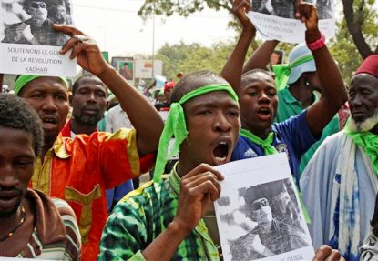 FILE - In this March 19, 2011 file photo, supporters of besieged Libyan leader Moammar Gadhafi cheer as they rally in support of him in the city of Bamako, Mali. While Western powers herald the death of Gadhafi, killed Thursday, Oct. 20, 2011, many Africans are mourning a man who poured billions of dollars of foreign investment into desperately poor countries. Gadhafi backed some of the most brutal rebel leaders and dictators on the continent, but tens of thousands are now gathering at mosques built with his money and are remembering him as an anti-colonial martyr, and as an Arab leader who called himself African. (AP Photo/Harouna Traore, File)