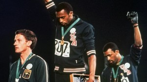 "In this Oct. 16, 1968, file photo, United States gold medalist Tommie Smith, center, and bronze medalist John Carlos, right, stare downward while extending their gloved hands skyward in racial protest alongside Australian silver medalist Peter Norman during the playing of ""The Star Spangled Banner."""