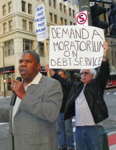 David Sole (r) holds sign while Rev. Charles Williams Sr. addresses rally against banks May 9, 2012.