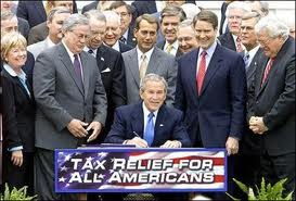 Bush signing his tax cut for the rich legislation.