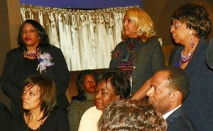 Krystal Crittendon (rear l) and sister and mother (rear r) wait in the wings at the outset of rally.