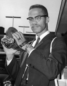 Portrait of American political activist and radical civil rights leader Malcolm X (1925 - 1965) as he holds an 8mm movie camera in London Airport, London, England, July 9, 1964. Shortly after breaking his affiliation with the Nation of Islam, and just days after his formation of the Organization of Afro-American Unity (OAAU), Malcolm X was in London en route to Egypt to attend a meeting of the Organization of African Unity and to meet with the leaders of various African states. (Photo by Express Newspapers/Getty Images)