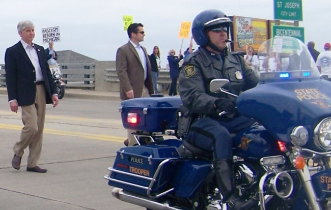 """""""Fascist:"""" Snyder on his way into Benton Harbor, the first victim of Public Act 4, on May 7, 2011. Hundreds protested."""