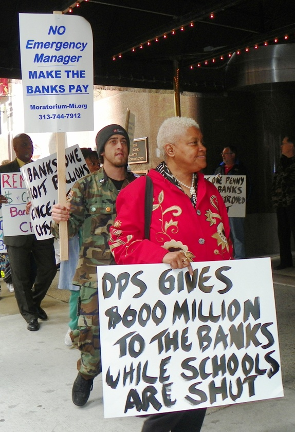 Maureen Taylor carries sign re: DPS during protest against banks' role in decay of Detroit and its schools May 9, 2012.