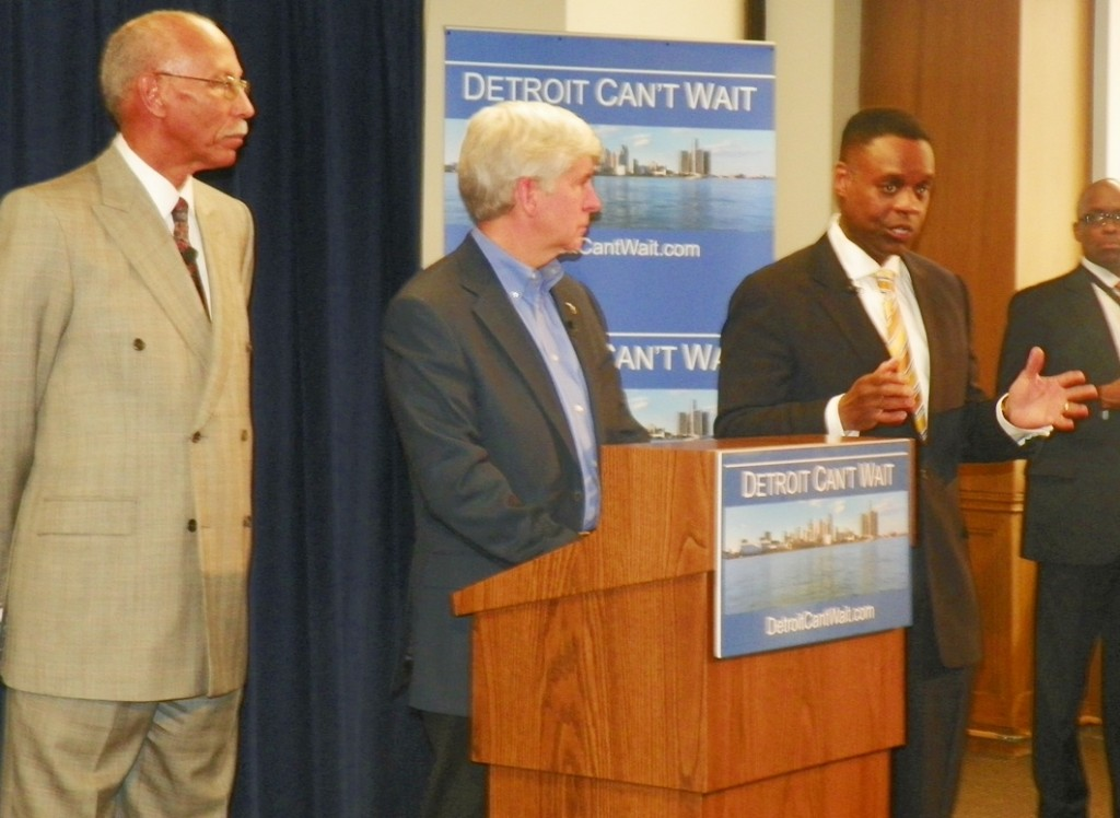 Kevyn Orr (r) addresses media at press conference March 14, 2013. Detroit Mayor Dave Bing and Michigan Gov. Rick Snyder (l to center) listen attentively.