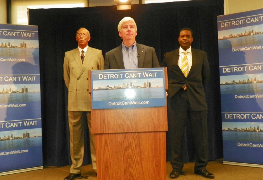 Michigan Gov. Rick Snyder (at podium) announces state takeover of Detroit, the world's larges Black majority city outside of Africa. Mayor Dave Bing (r) and new EFM Kevyn Orr stand at attention during press conference March 14, 2013.