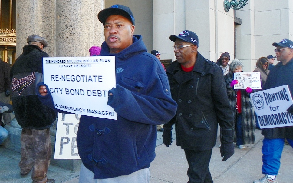 Protester outside EM press conference Marcy 14, 2013 calls on city to confront banks.
