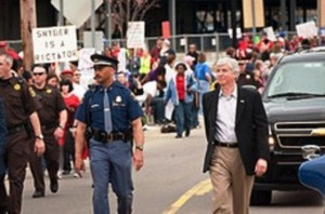 "Protesters swamped Gov. ""Rictator"" Snyder during Benton Harbor's annual Blossomtime Parade last year, calling him a ""dictator.:"
