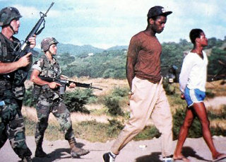 U.S. soldiers with captive citizens of Grenada, a predominantly Black, socialist-led country..