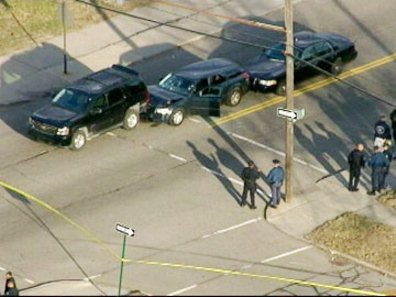 Matthew Joseph's car in between two unmarked police cars. This aerial photo was taken some time after his killing. It shows police crime tape roping off the scene and does not appear to show him still in the car, accounting for the open car door.