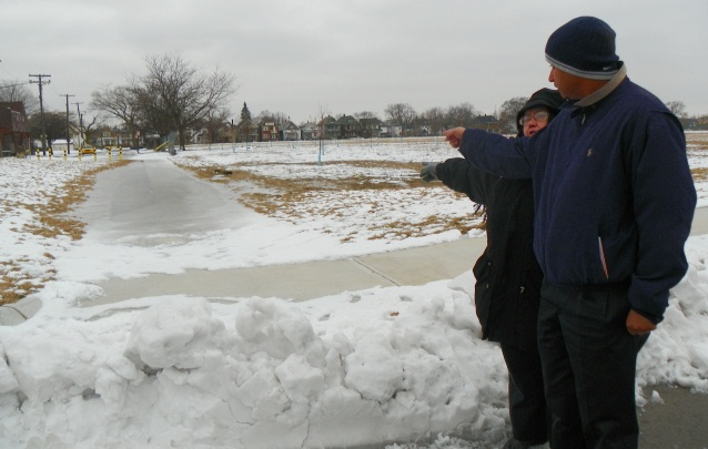 Sheila Crowell and neigbhor point out iced over walkway on Munger grounds that they fear will melt in the spring and contaminate new soil laid over old.
