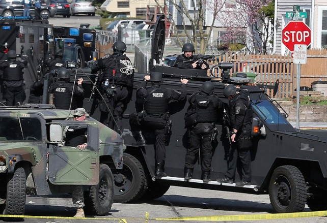 Military-style manhunt for bombing suspect in Boston suburbs April 19, 2013. News media are championing paramilitary  forces involved, saying this incident should convince U.S. public to cede their civil liberties in some circumstances.