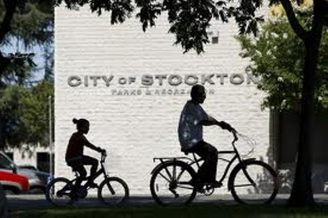 Children ride their bikes past a City of Stockton recreational building.