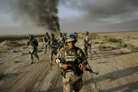 An Iraqi army soldier, accompanied by U.S. army soldiers from Fox Troop, Sabre Squadron, 3rd Armored Cavalry Regiment, walks down a field as plumes of smoke rise from a burned irrigation canal in a deserted area on the outskirts of Balad Ruz, in Iraq's Diyala province, some 75 kilometers ( miles) northeast of Baghdad, Iraq, Sunday, Aug. 10, 2008. Soldiers from Fox Troop burned thick growth inside irrigation canals as they were searching for weapons caches in the area. (AP Photo/Marko Drobnjakovic)