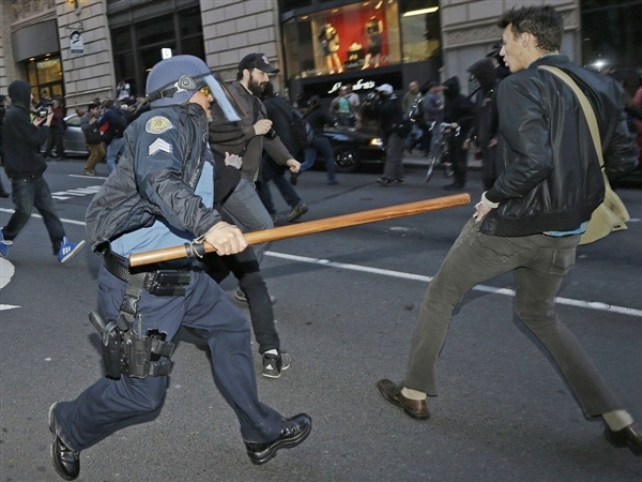 A Seattle Police officer with a baton tries to fend off protesters during a May Day anti-capitalism protest that ended with demonstrators clashing with police on Wednesday. Ted S. Warren / AP