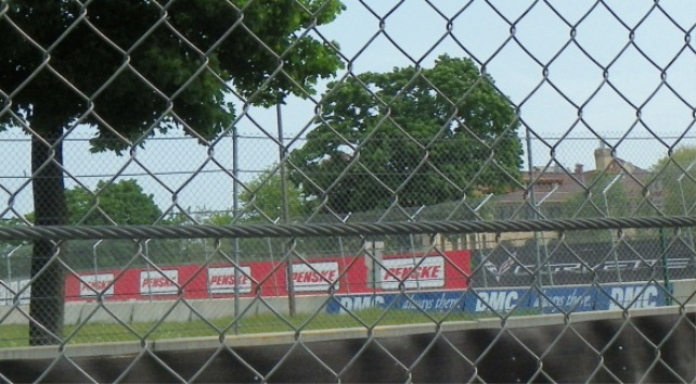 Fences and barricades protect the wealthy coming to see the Grand Prix.