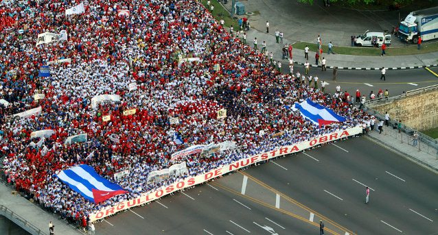 """People hold a banner that reads in Spanish """"Proud of our work"""" at the front of the May Day march to Revolution Square in Havana, Cuba, Wednesday, May 1, 2013. AP / Ismael Francisco"""