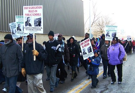 Child carries sign: Jim Crow is dead, during Dr. MLK Day march in 2011 from Dr. Martin Luther King, Jr. High School.