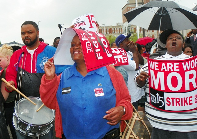 MacDonald's worker shiields herself from rain as drummer gives rhythm to chants.