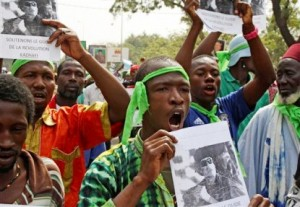 In this March 19, 2011 file photo, supporters of besieged Libyan leader Moammar Gadhafi cheer as they rally in support of him in the city of Bamako, Mali. While Western powers herald the death of Gadhafi, killed Thursday, Oct. 20, 2011, many Africans are mourning a man who poured billions of dollars of foreign investment into desperately poor countries. Tens of thousands are now gathering at mosques built with his money and are remembering him as an anti-colonial martyr, and as an Arab leader who called himself African. (AP Photo/Harouna Traore, File)