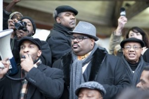 Rev. David Bullock speaks at  MLK Day, 2012 march on Gov. Rick Snyder's house, with Rev. Charles Williams II at his left. Also present (top) Rev. Charles Williams, Sr. (r) Rev. Edward Pinckney.