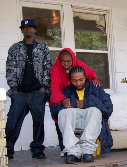 The morning of Aiyana's death, Charles Jones is comforted by his aunt JoAnn Robinson, now deceased, and her son Mark Robinson. Mark warned the raid team there were children in the house before they entered; toys were strewn on the front yard. Behind Mark's head is window shattered by stun grenade; couch where Aiyana died is next to Charles.