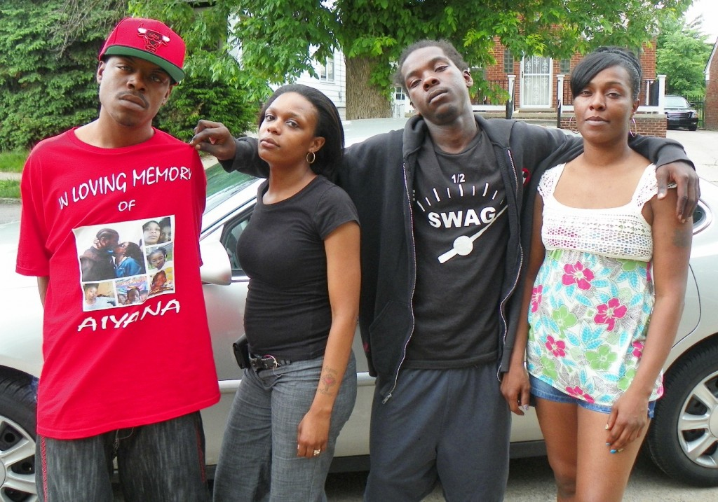 Aiyana Jones' mother Dominika Jones (second from left,) with her uncle Dazmond Ellis (l), cousin Markewell Robinson, and aunt La'Kia Sanders gather outside family home May 29, 2013, the evening the trial against her killer, Officer Joseph Weekley, began.
