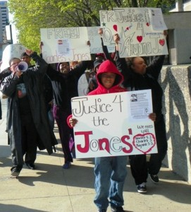 Rafael Jones, 14, leads march for Justice for Aiyana and Charles Jones April 23 2012 at Frank Murphy Hall in downtown Detroit, grandmother Mertilla Jones at left, aunt LaKrystal Sanders at right. Sanders lived upstairs from the Jones family.
