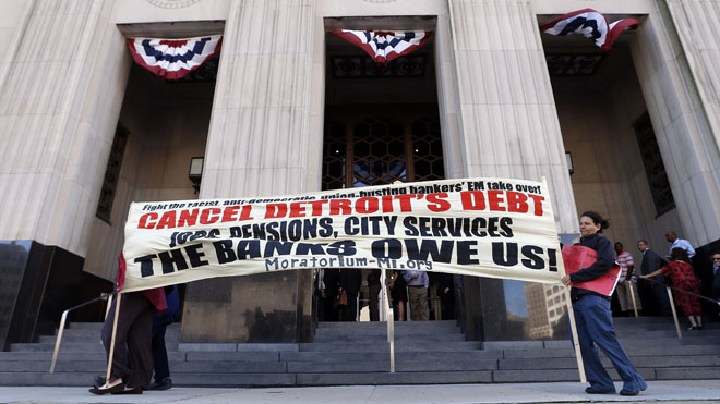Protesters carry a sign outside the Levin Federal Courthouse in Detroit, Wednesday, July 24, 2013. .(AP Photo/Paul Sancya)