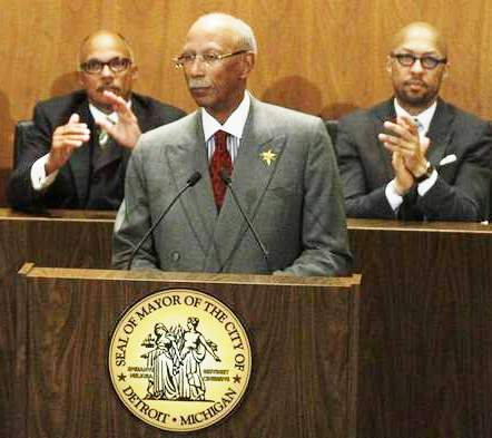 Former Council member Gary Brown, now Chief Compliance Officer under Kevyn Orr, applauds Detroit Mayor Dave Bing. At right is former Council Pres. Charles Pugh, who has disappeared after an alleged sex scandal.