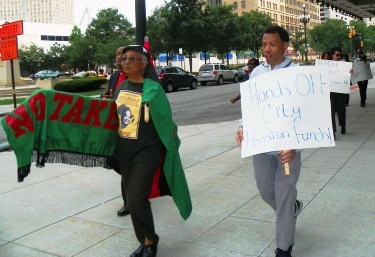 Fourth of July protest demanding independence for Detroit at Orr's residence at the Westin Book-Cadillac. One protester demands, Hands off city pension funds.