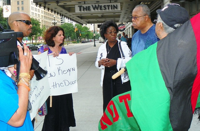 Detroit city retiree and union rep Carrie Williams (center) with husband at her left, speak with protesters.