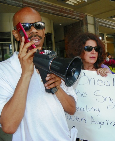 Richard Clay calls hotel to announce boycott; Detroit School Board member Elena Herrada is at right.