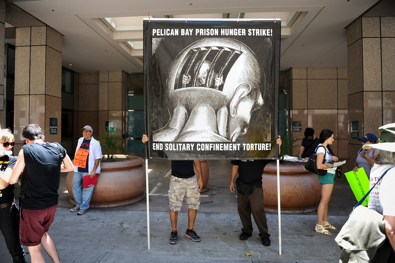 A pair holds a solitary confinement protest sign outside the Ronald Reagan State Building in downtown L.A. Monday, July 8, 2013, during a protest against solitary confinement in California prisons. (Michael Owen Baker/L.A. Daily News)