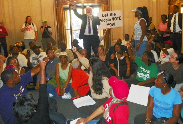 Protesters sit-down in Cadillac Place lobby June 28, 2012 to demand vote on PA 4, which was overwhelming rescinded. Snyder et al replaced it with PA 436 in the dark of the night..