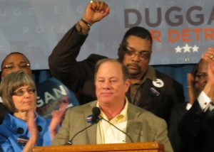 Duggan's long-time ally Min. Malik Shabazz behind him at rally.