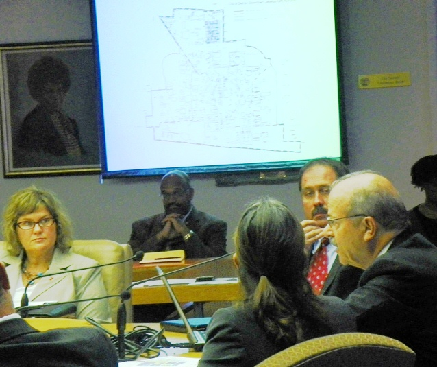Art Papapanos (r) of the DEGC presents Illitch stadium proposal to Council committee Sept. 5, 2013. Slide shows proposed new DDA boundaries and project area. Next to it is portrait of the late City Council President Erma Henderson.