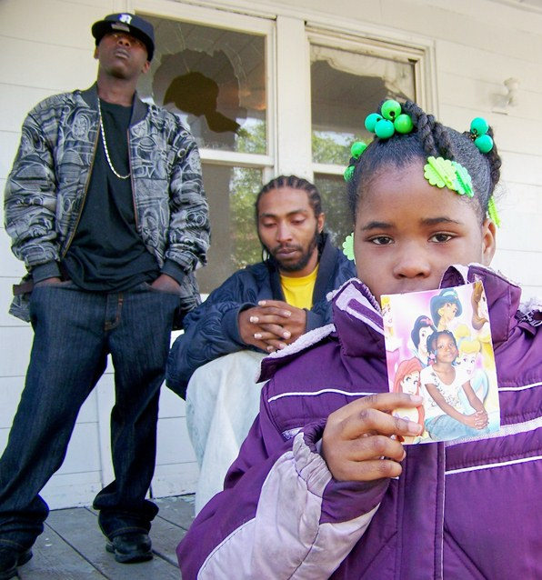 Mark Robinson (l) with Aiyana's father Charles Jones, classmate Diamond Hardy, showing her photo, on morning of her death May 16, 2010.