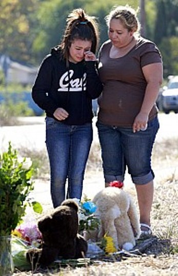 Maria Chavez comforts daughter Yaritz Romez, 14, at memorial. Photo Beth Schlanker PD