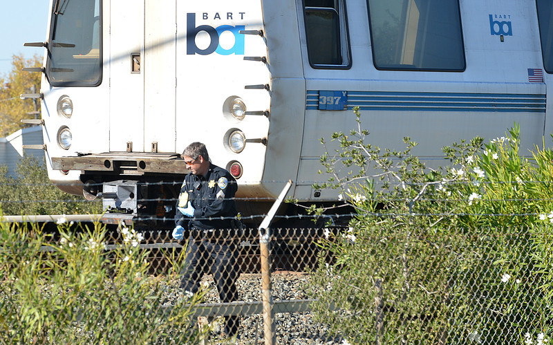 A BART police officer looks along the outside of a BART car that struck and killed two people along Jones Road in Walnut Creek, Calif., on Saturday, Oct. 19, 2013. (Dan Rosenstrauch/Bay Area News Group)