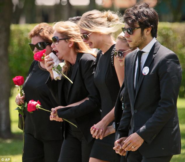 Teen's mother Jacqueline Llach, with flower to face, sobs at funeral.