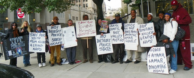 Families display signs outside courthouse (l to r) Gabrielle and Dominique Harrison, Oct. 22 protester, Khalid Fareed, Roberto Guzman, unnamed, Gary of Oct. 22nd, Herman Vallery, Cornell Squires, unnamed, daughter of Taminko-Sanford-Tilmon at her left, Jermaine Tilmon, with grandson Omari.
