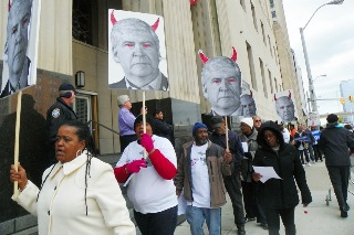 Detroit city retirees protest Detroit bankruptcy filing outside federal court Oct. 28, 2013. Signs depict Michigan Gov. Rick Snyder as the devil. He teamed up with Wall Street banks represented by Jones Day law firm, which has been hired to represent the city, to attack assets and pensions of the city through Chapter 9 bankruptcy.