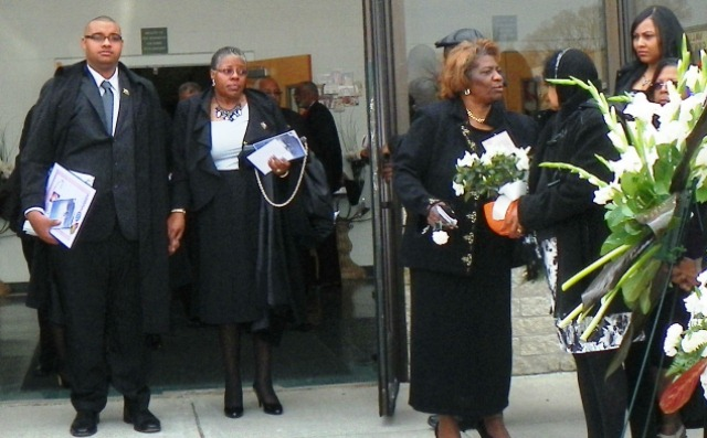 Attorney Gail Wilson (second from left), a member of the Official Retirees Committee, leaves funeral for her husband, renowned Pres. Leamon Wilson of bus mechanics Local 312, with son Leamon E. Wilson at side April 15, 2013.
