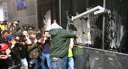 Protester smashes windown at RBS branch in London during mass uprising against austerity measures there.