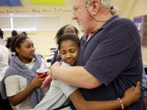 Student hugs teacher at Hutchins as second waits her turn.