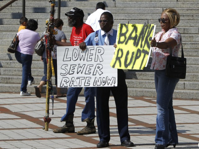 Protesters in Birmingham, Ala. denounce increase in sewage rates that was part of Mongtomery County's exit from bankruptcy. JPMorgan Chase, guilty of massive bond fraud, was also forced to cut its debt payments from the County by 75 percent.