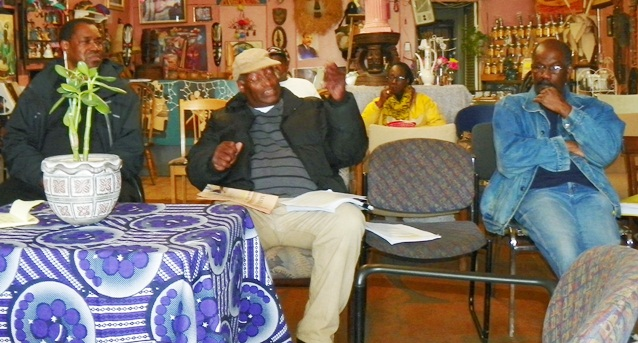 Retiree Hassan Aleem (speaking with others including Carl Williams (r) at N'namdi meeting.