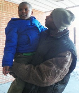 "Arthur Simmons, Jr. holds child during DHS visit, after the little boy ran outside crying, ""DADDY, DADDY!"""